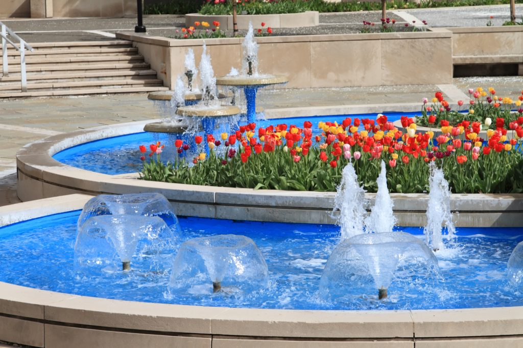 A fountain with red and orange flowers located in downtown Peoria IL